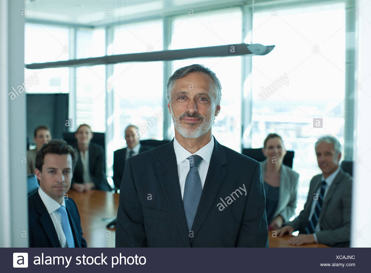 Portrait of smiling businessman and co-workers in conference room Stock Photo