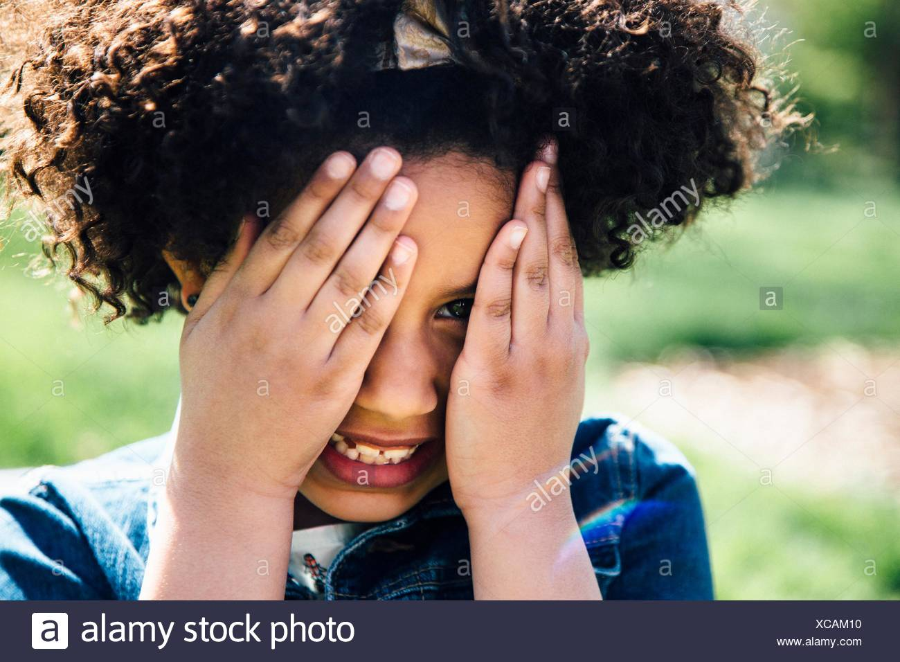 Close up portrait of girl covering face with hands - Stock Image