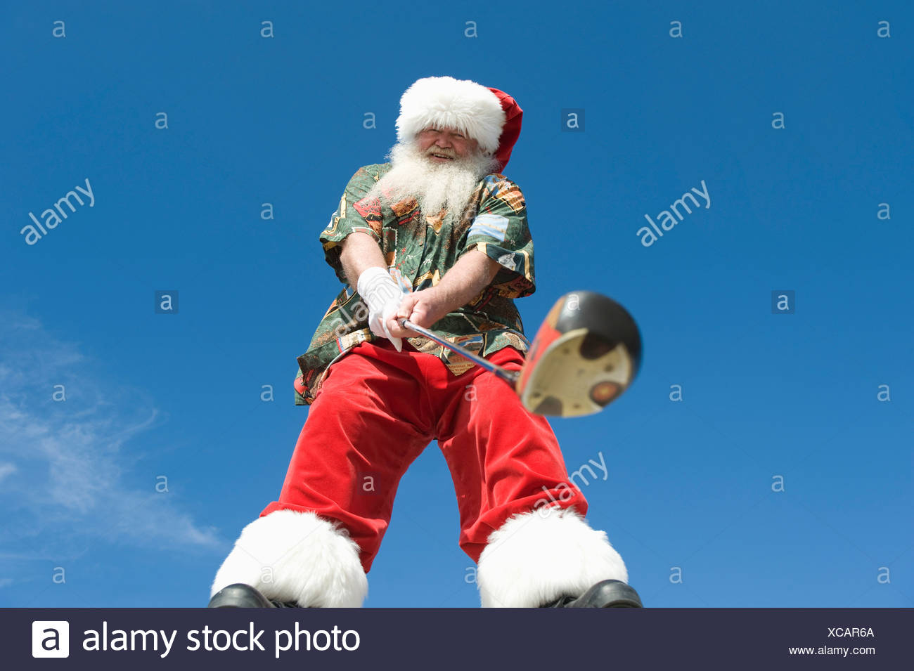 Father Christmas stands with gold club Stock Photo