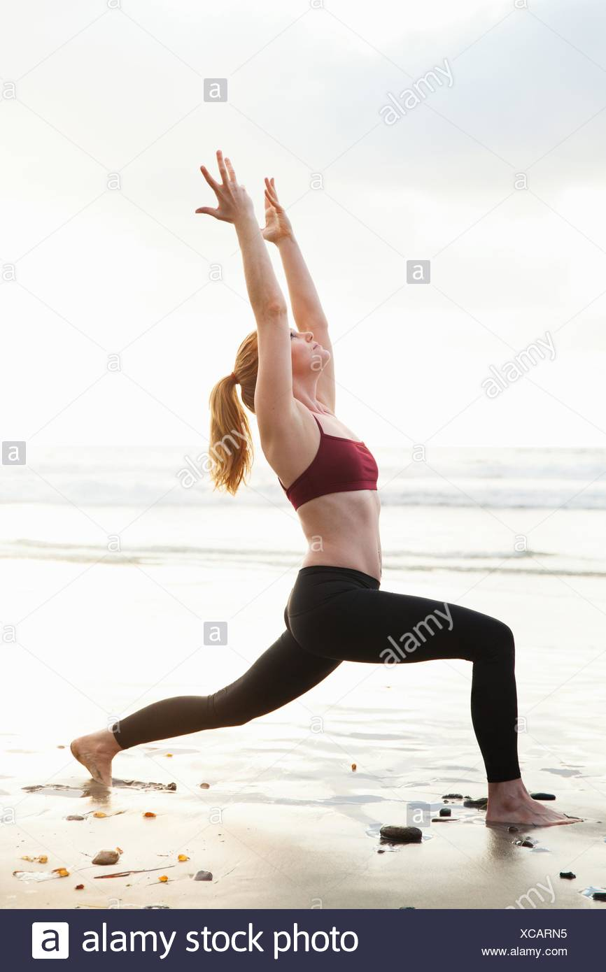 Mid adult woman practicing warrior pose with arms raised on beach - Stock Image