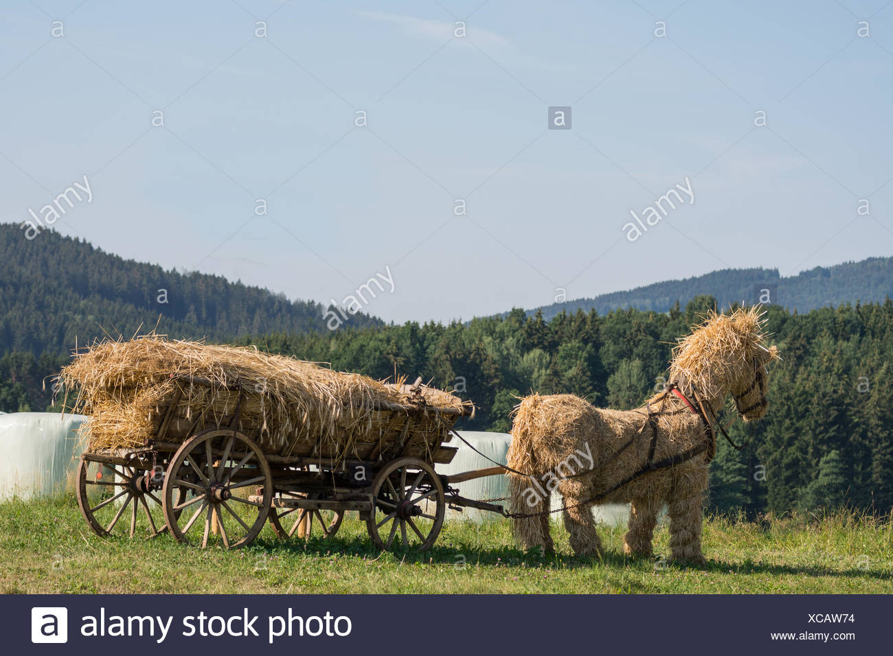 Straw horse inflated with thatched wooden wagon in the open countryside - Stock Image