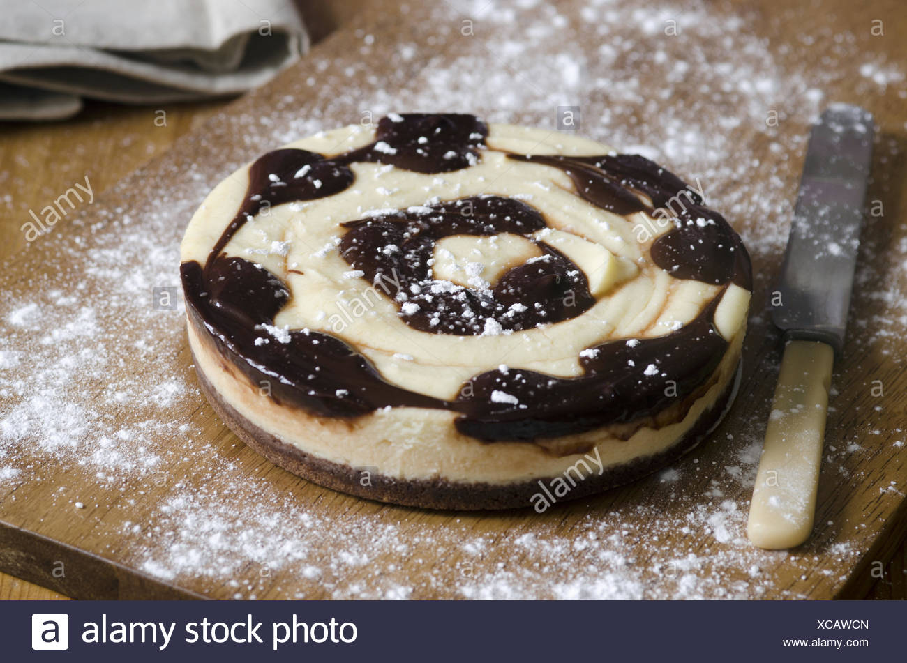 Delicious chocolate swirl cheesecake on a wooden board. - Stock Image