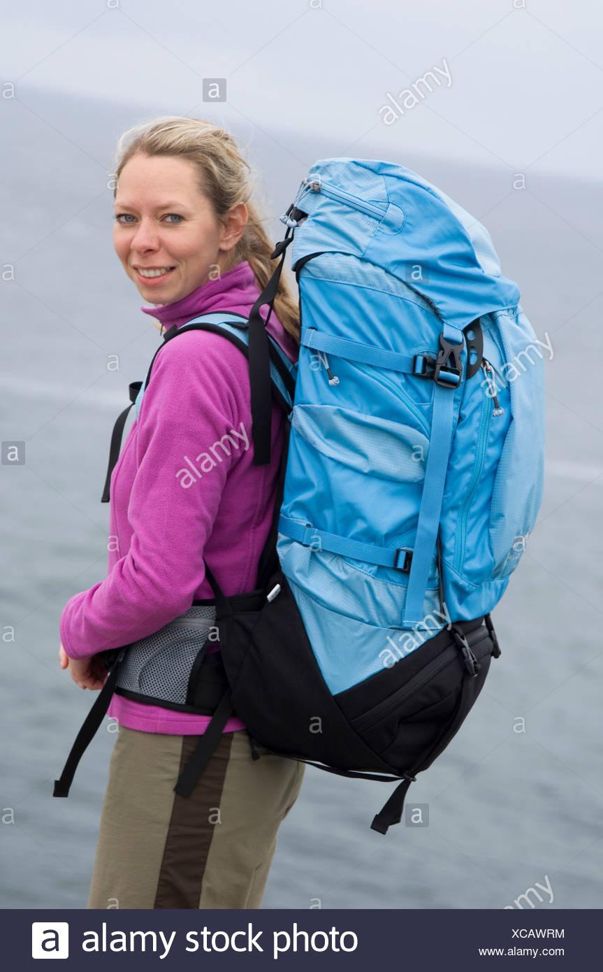 Portrait of backpacker near ocean. - Stock Image
