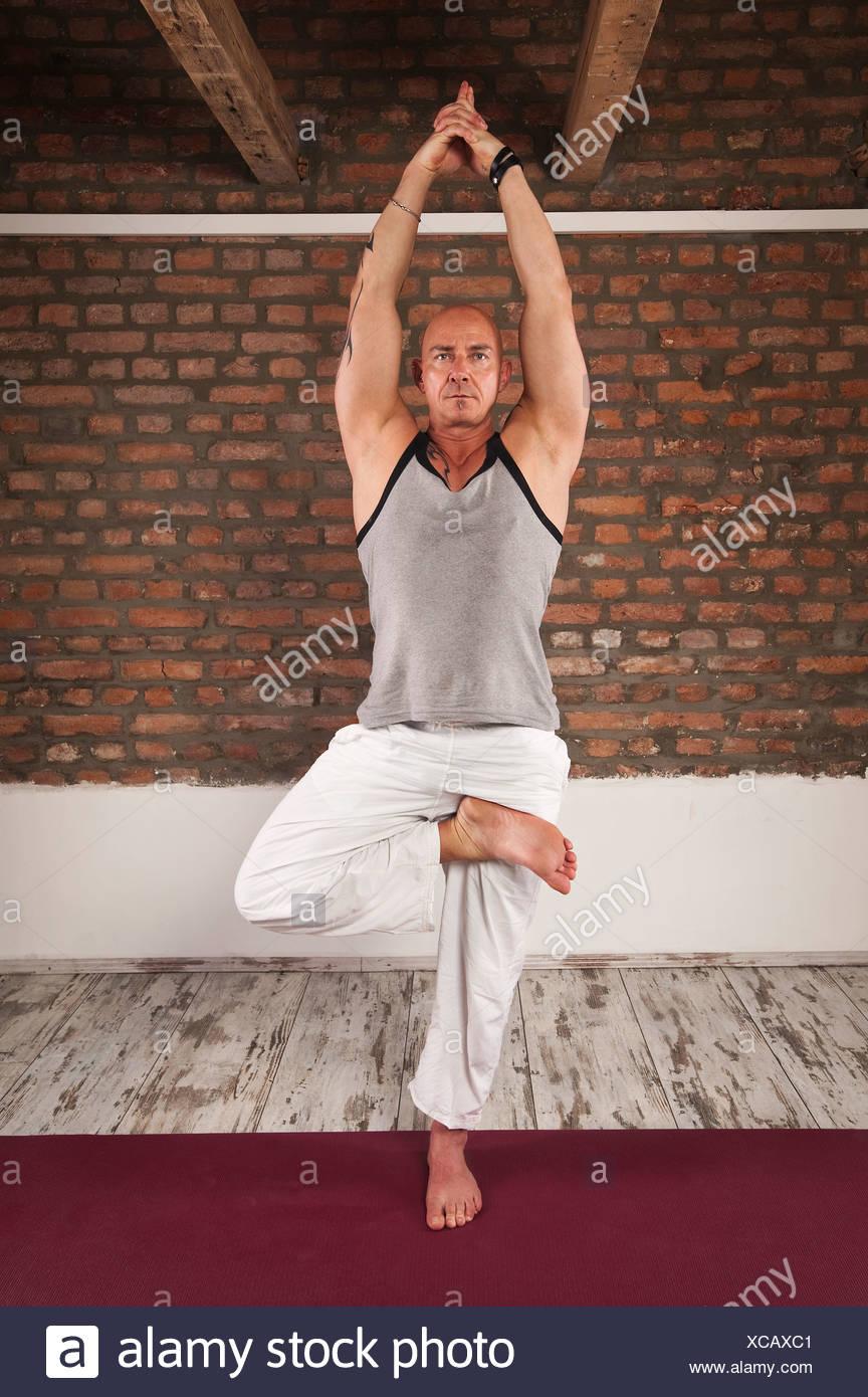 Man Practising Yoga, Tree Pose - Stock Image