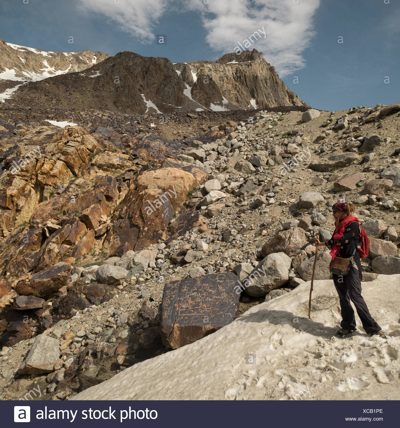 A European woman looks at Tibetan hieroglyph on a high mountain pass. - Stock Image