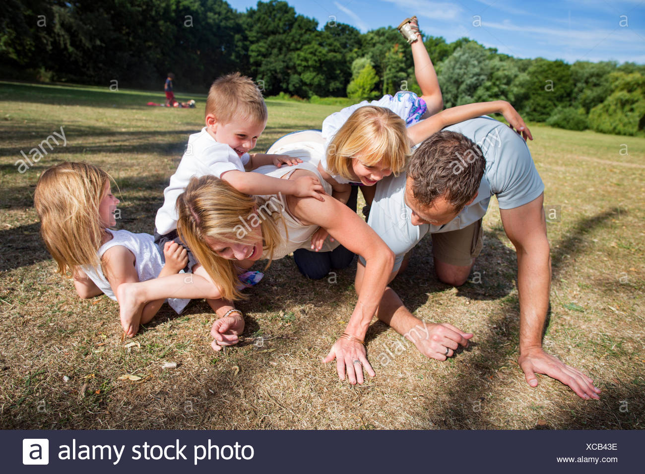 Family with three children playing in a park. Stock Photo