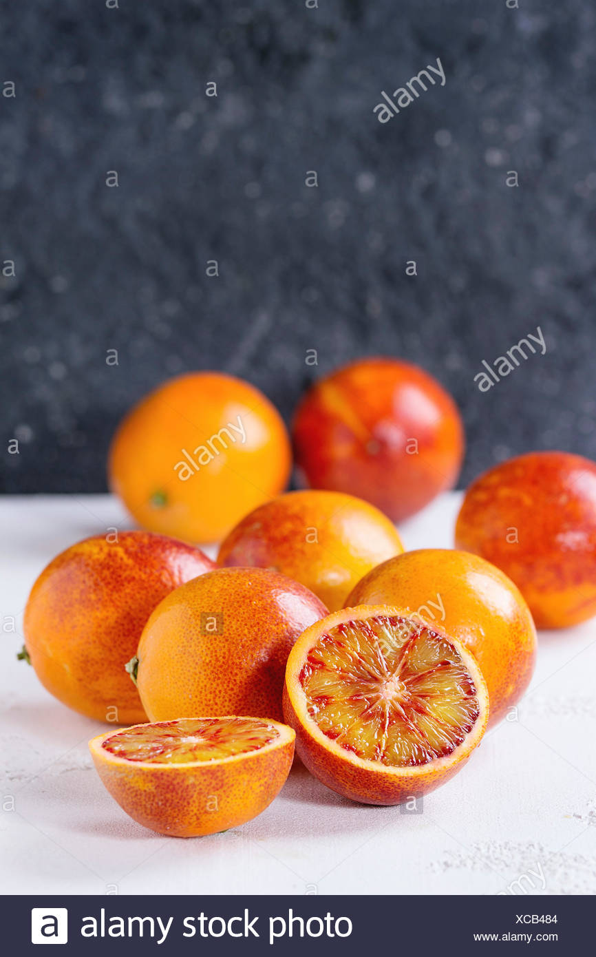 Sliced and whole ripe juicy Sicilian Blood oranges fruits over white and gray concrete texture background. Copy space - Stock Image