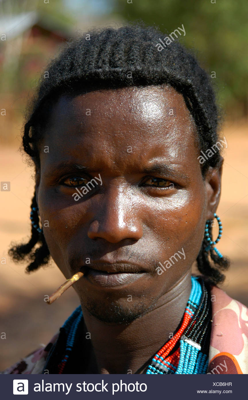 Man chewing on a stick, portrait, at the markets in Dimeka, Ethiopia, Africa - Stock Image