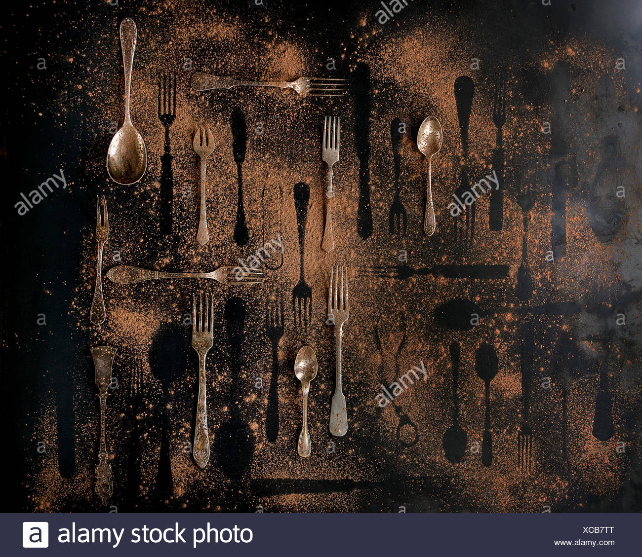 Big set of vintage and disappeared cutlery under brown dust over black metal background. Top view - Stock Image