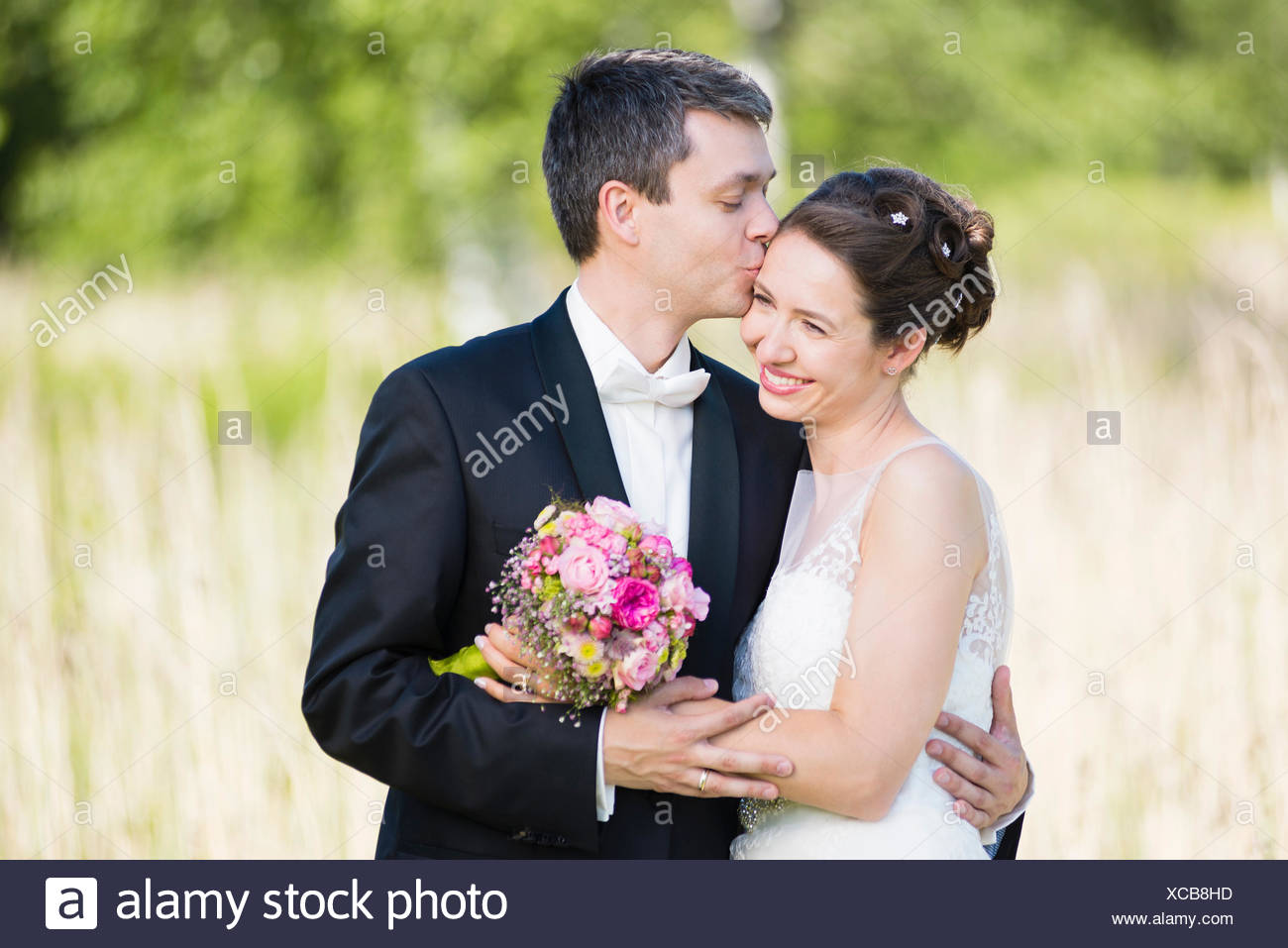 Portrait of romantic newlywed mid adult couple in park - Stock Image