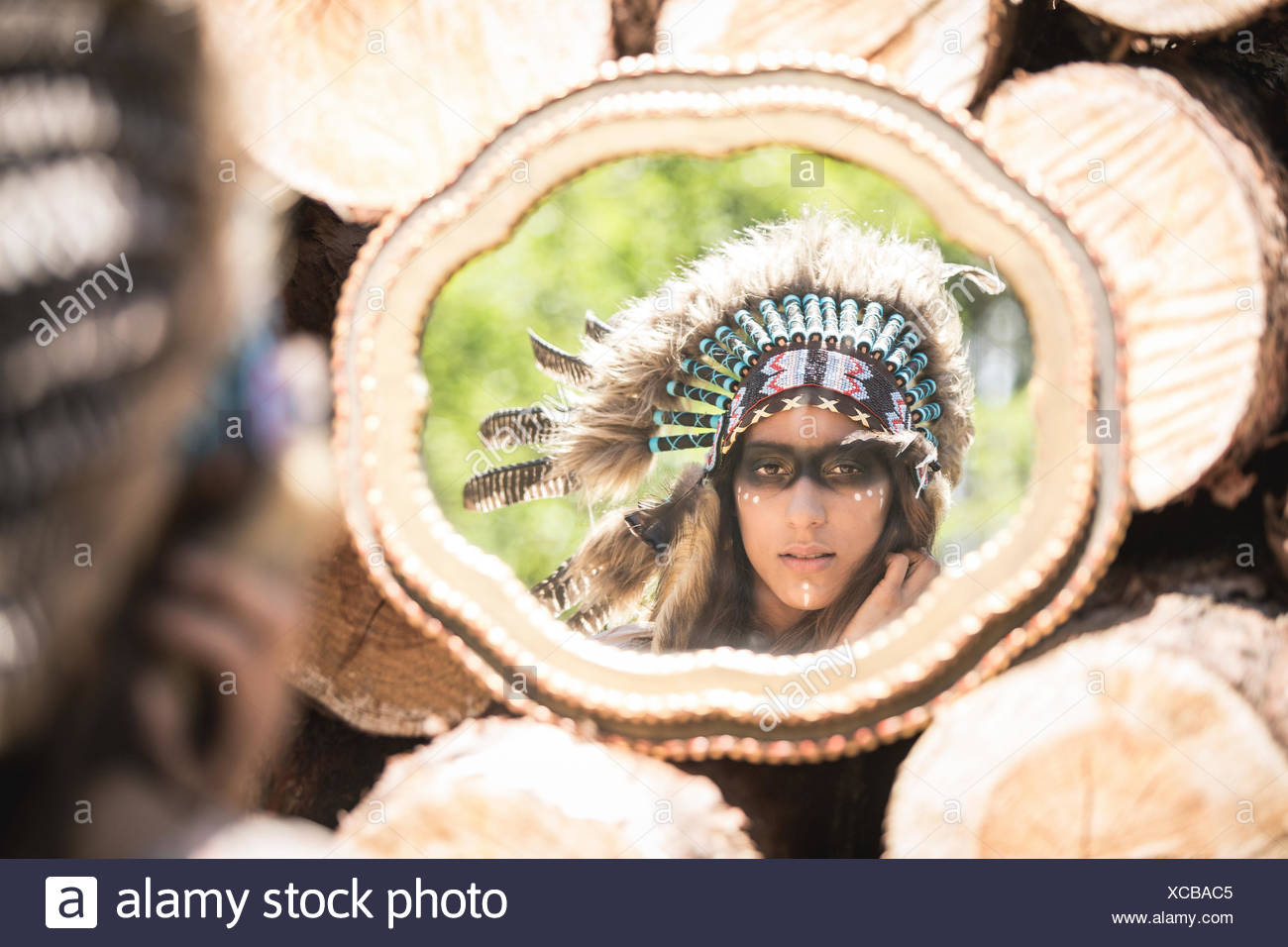 Mirror image of young woman masquerade as an Indian - Stock Image