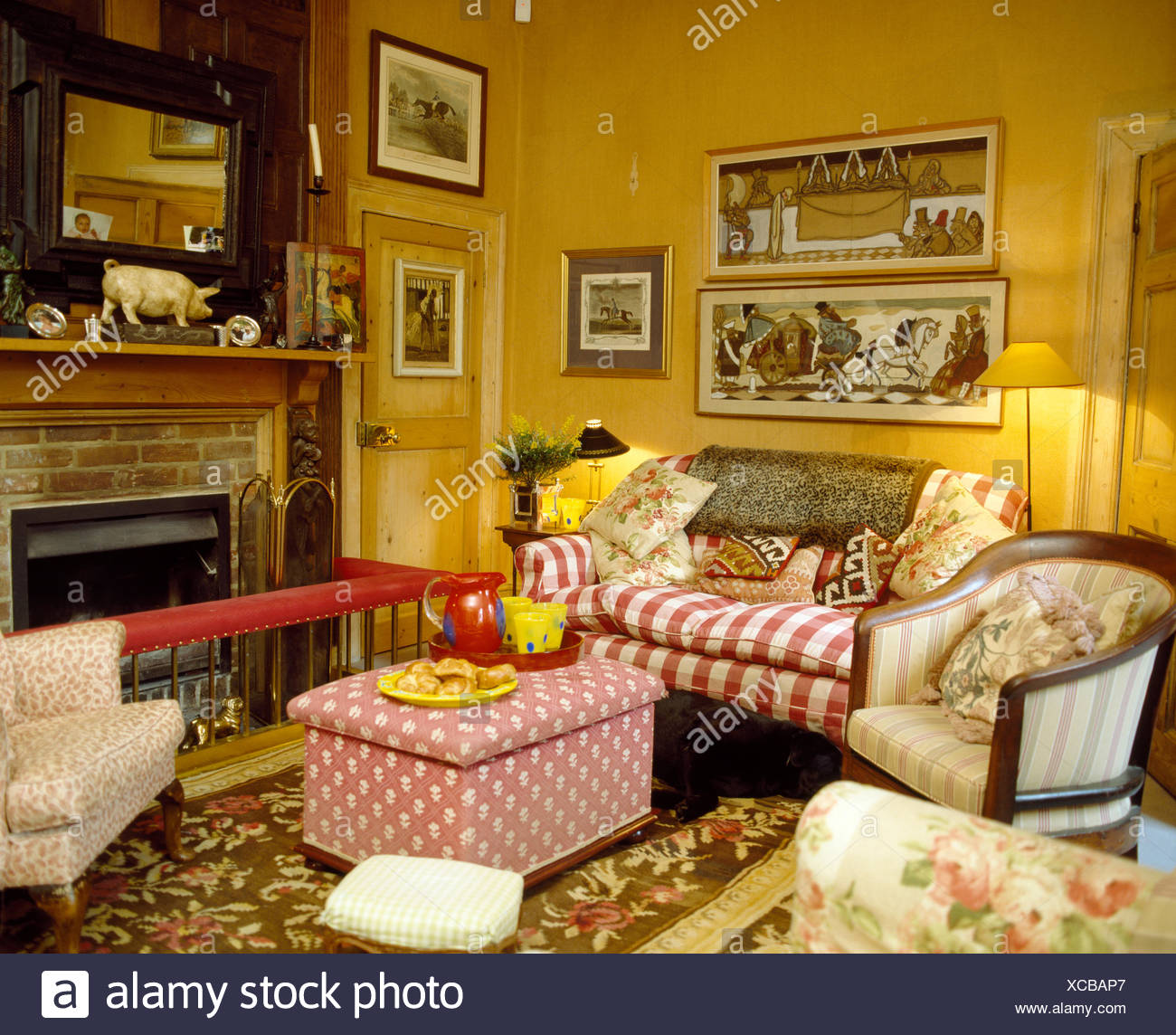 Pictures above red striped sofa in country living room with pink ...