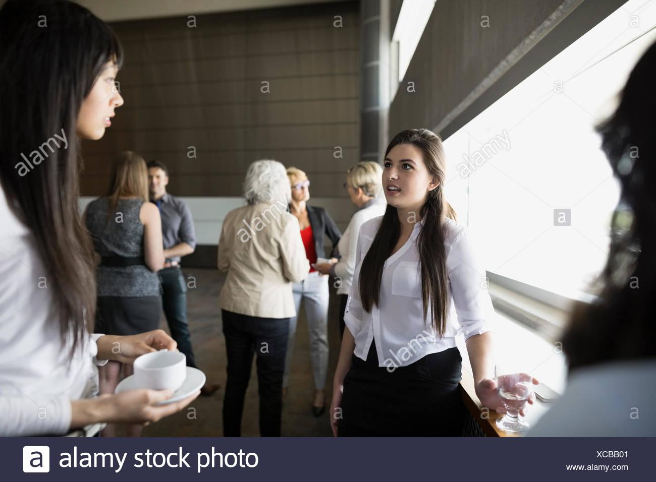 Women socializing in auditorium - Stock Image