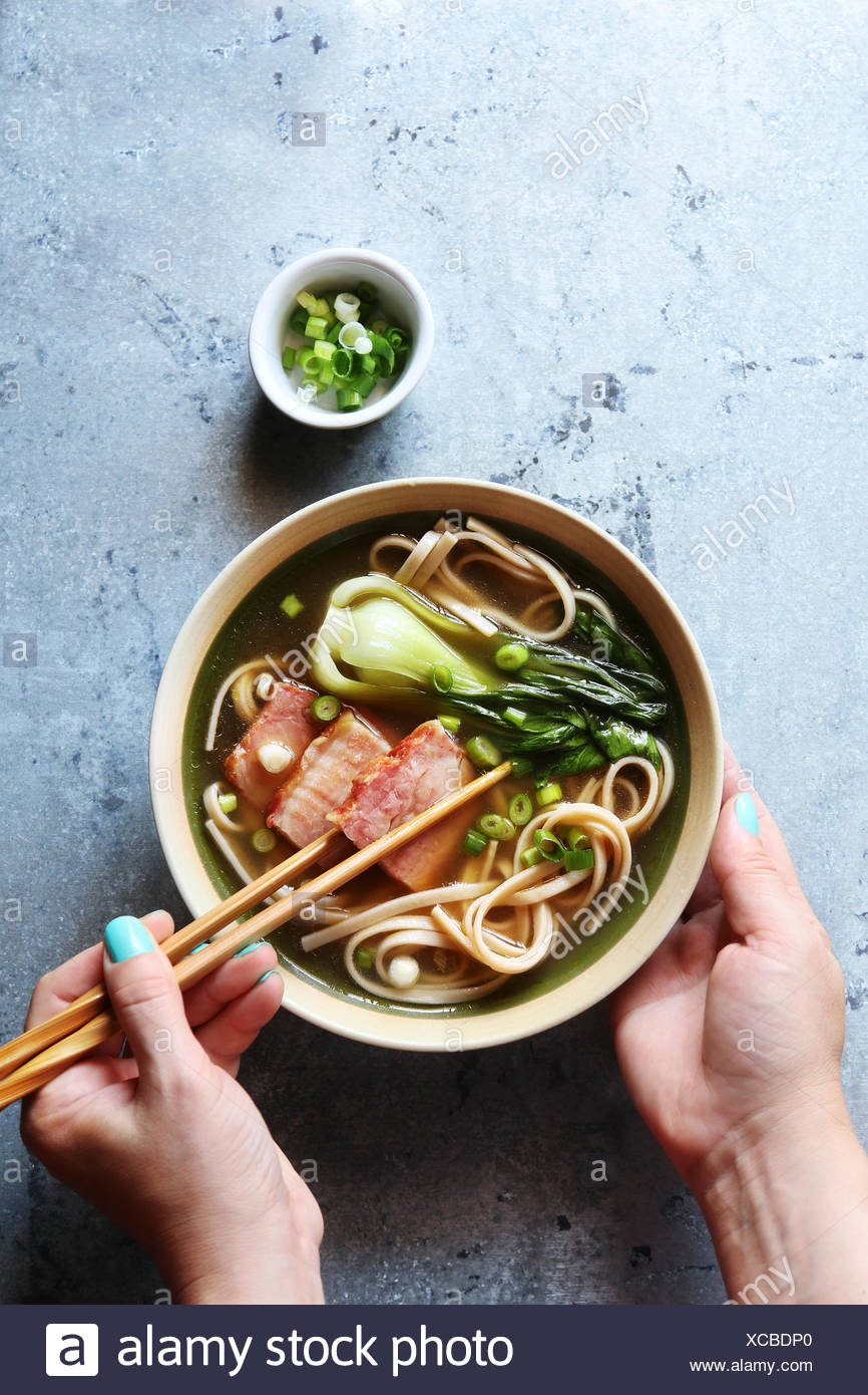 Female hands holding a bowl of pork belly udon noodle soup.Top view - Stock Image