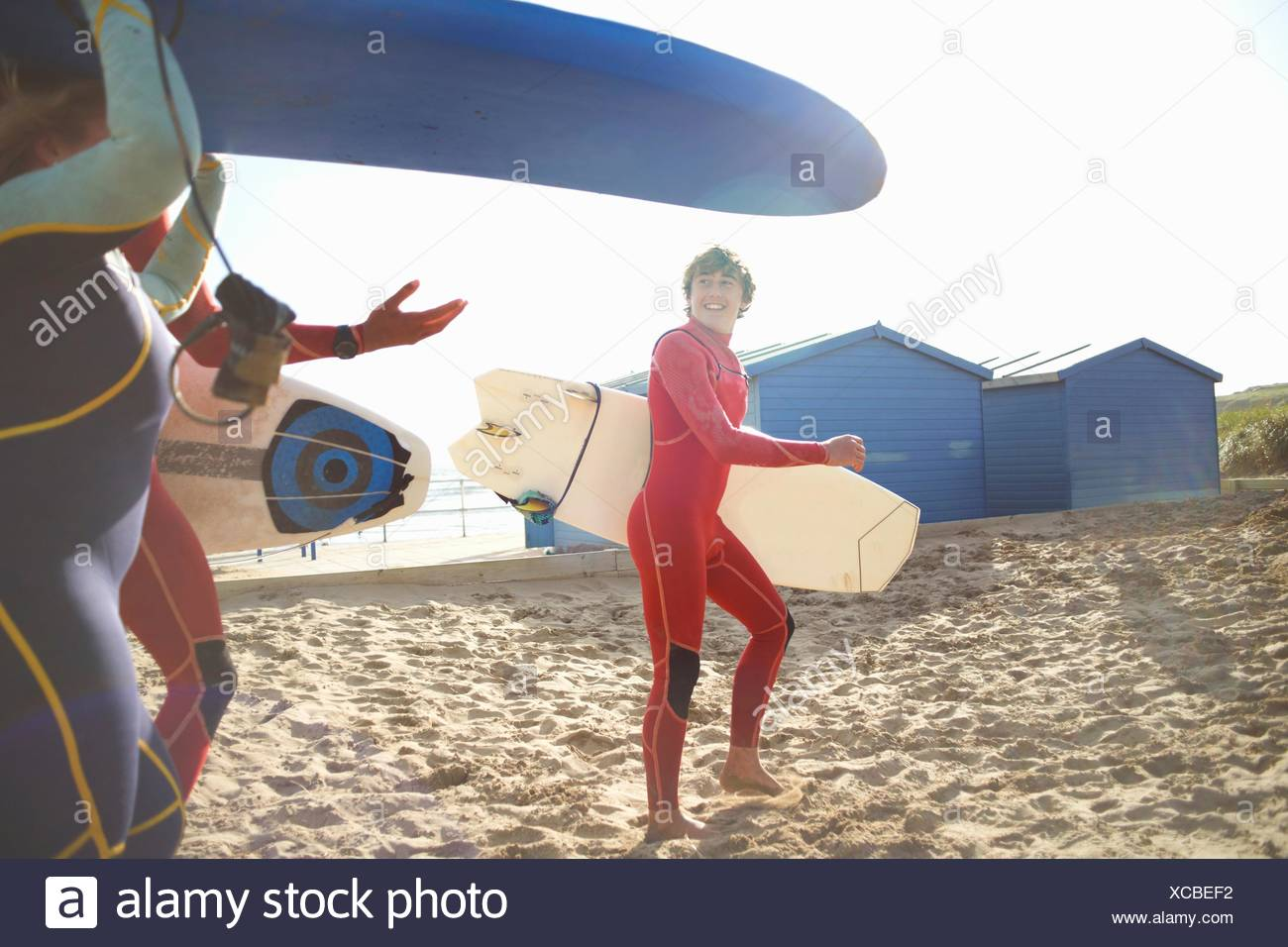 Group of surfers on beach, carrying surfboards - Stock Image