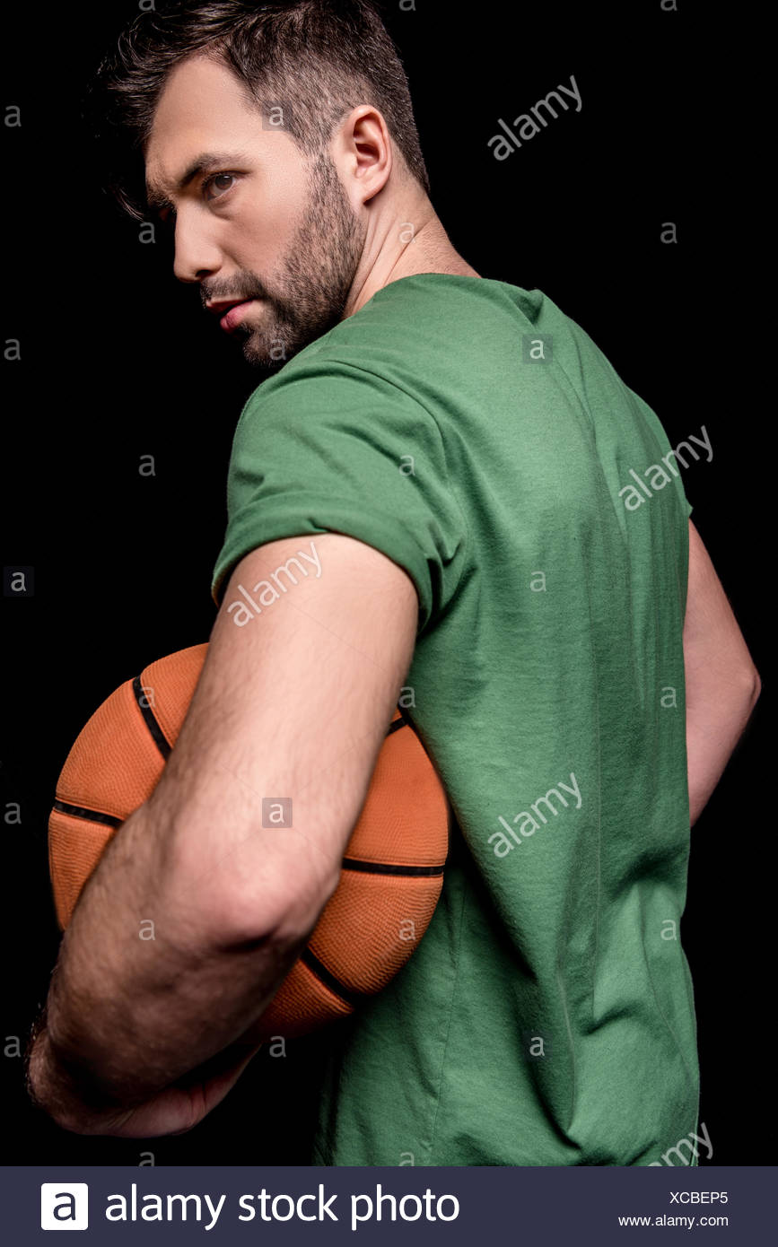 back view of man holding basketball ball and looking away on black - Stock Image