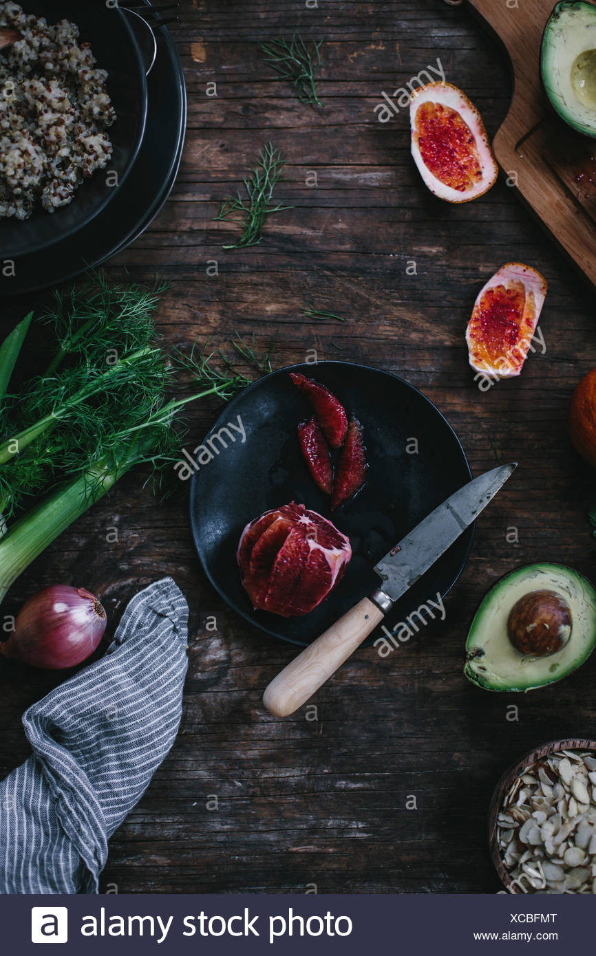 Sliced blood oranges are surrounded with cooked quinoa avocado sliced almonds fennel and a shallot. Photographed on a reclaim - Stock Image