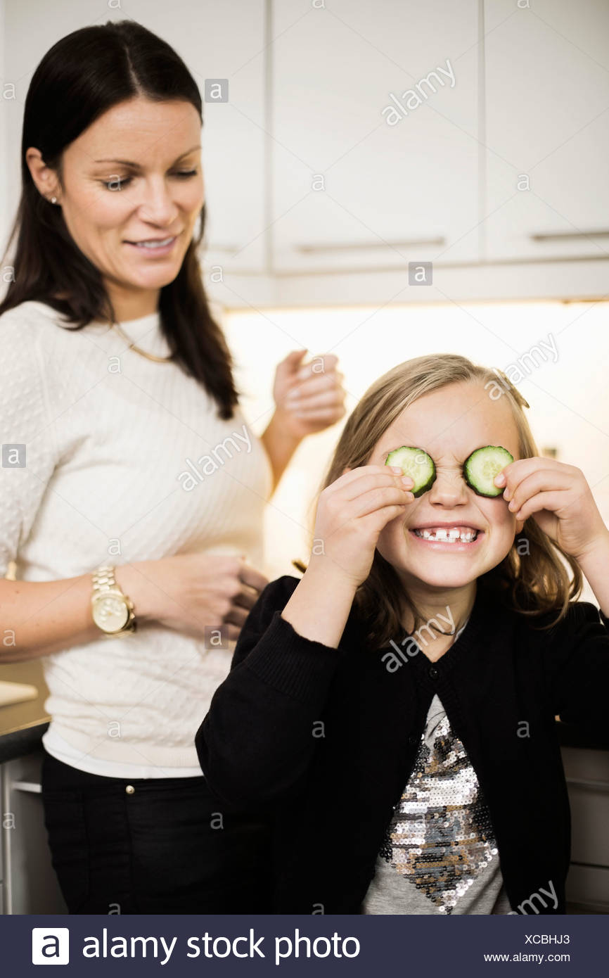 Mother looking at daughter covering eyes with cucumber slices Stock Photo