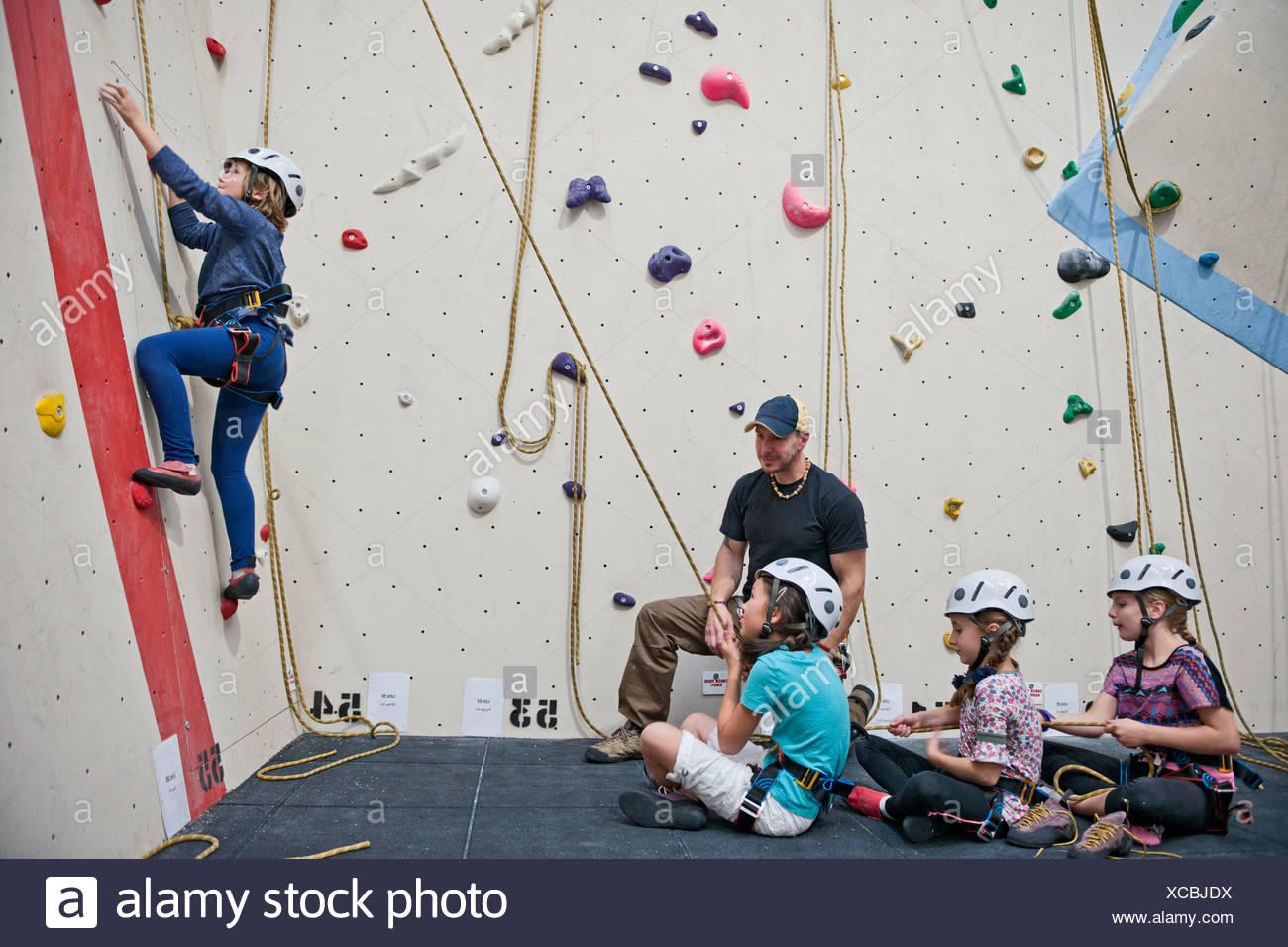 Male instructor working with group of children on climbing wall - Stock Image