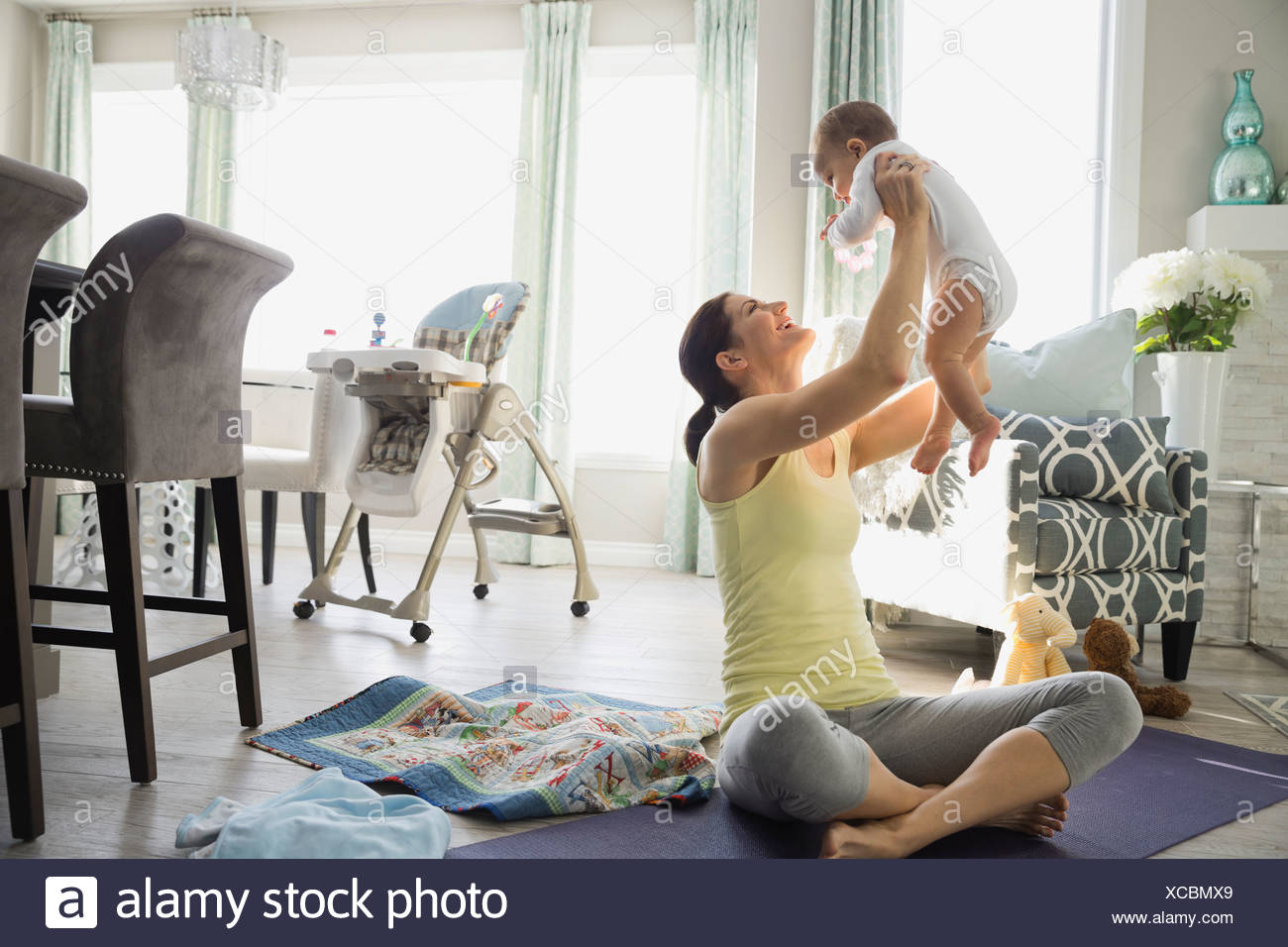 Fit mother lifting baby on exercise mat at home - Stock Image