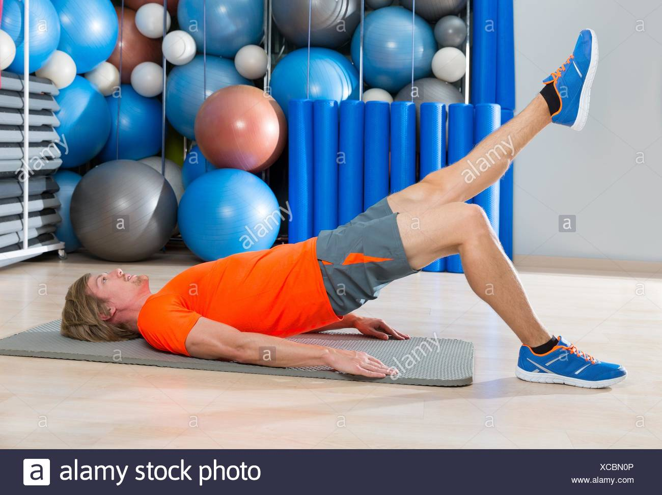 hip lift with leg extension blond man at gym workout with swiss ball background. - Stock Image