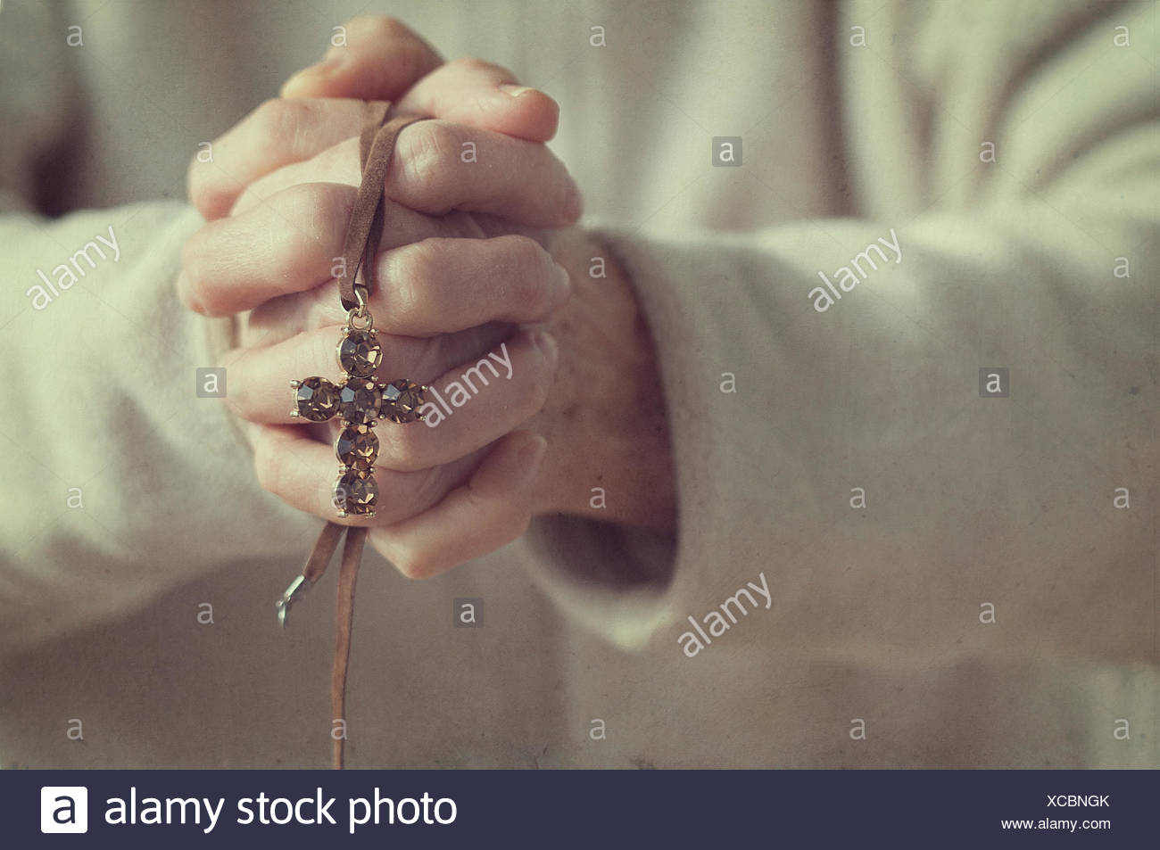 Senior woman with hands clasped holding a crucifix - Stock Image