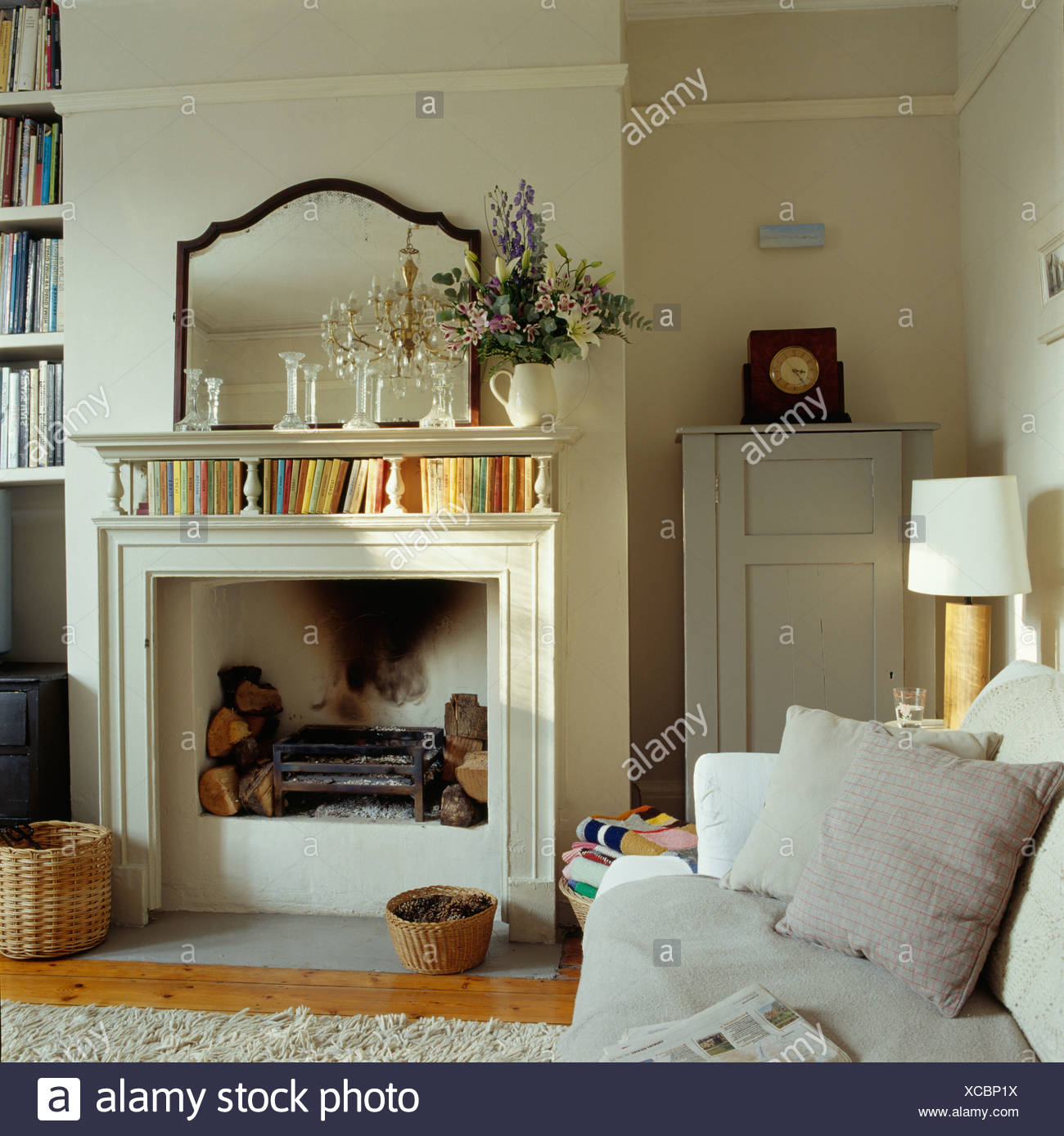 Antique Mirror Above Cream Fireplace In Cream Country Living Room With Painted Cupboard In Alcove Stock Photo Alamy