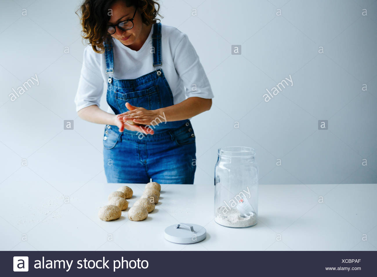Girl forming dough for bagels on a white table - Stock Image