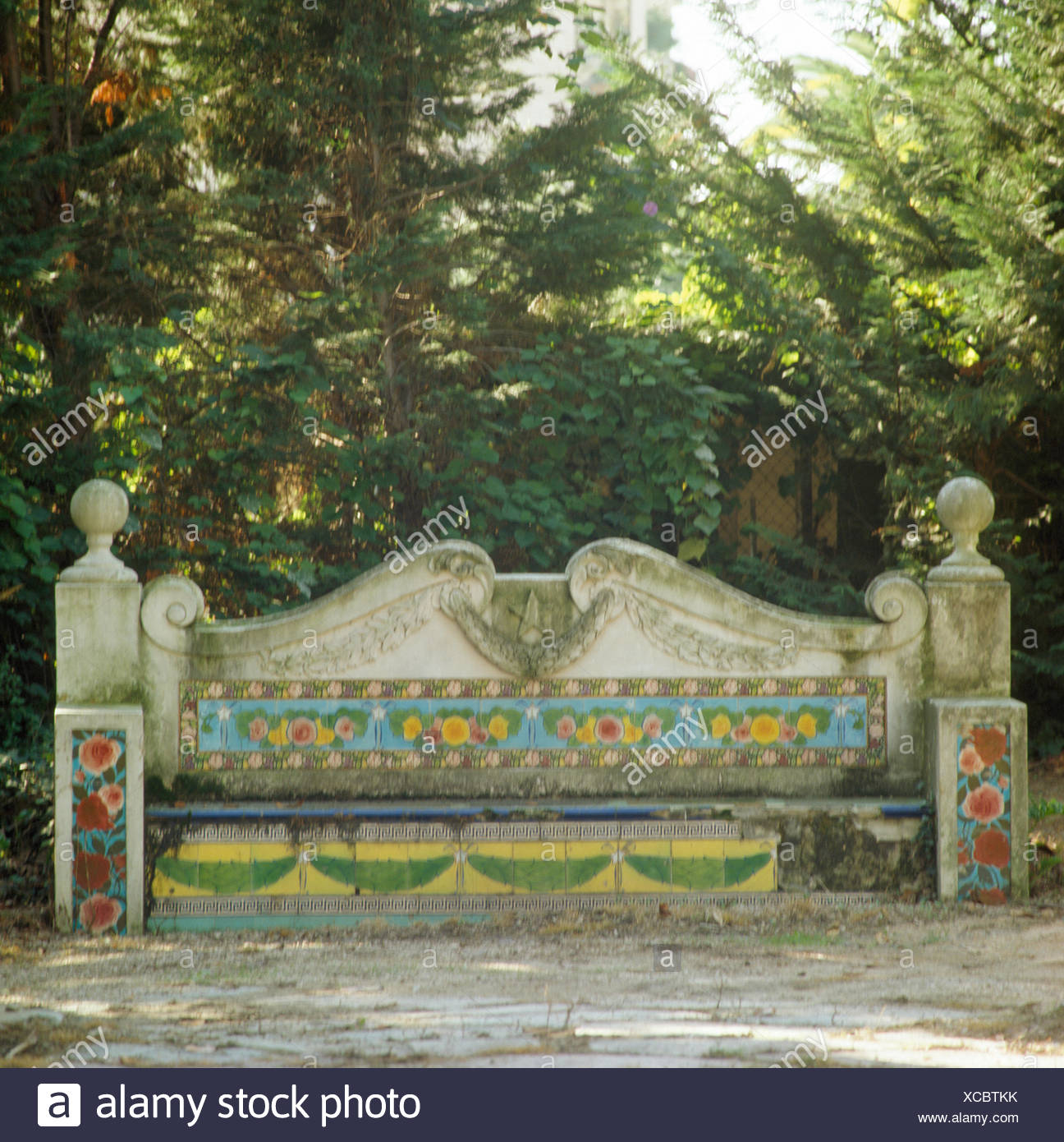 Stone seat with decorative tiles in large Italian garden - Stock Image