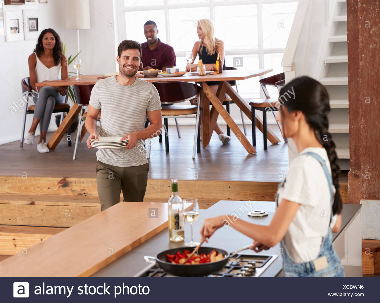 Friends Prepare And Serve Food For Dinner Party At Home Together - Stock Image