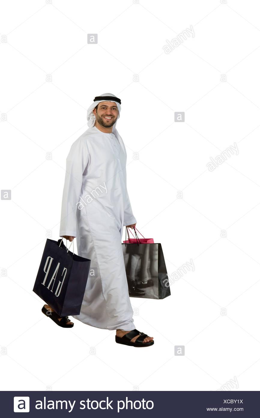 Arab man with shopping bags walking Stock Photo