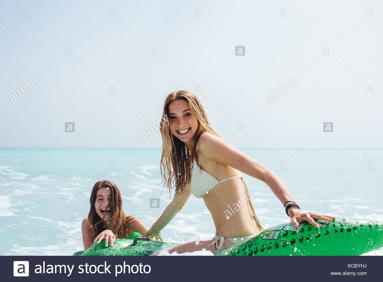 Portrait of two young female friends wearing bikinis playing on inflatable crocodile in sea - Stock Image
