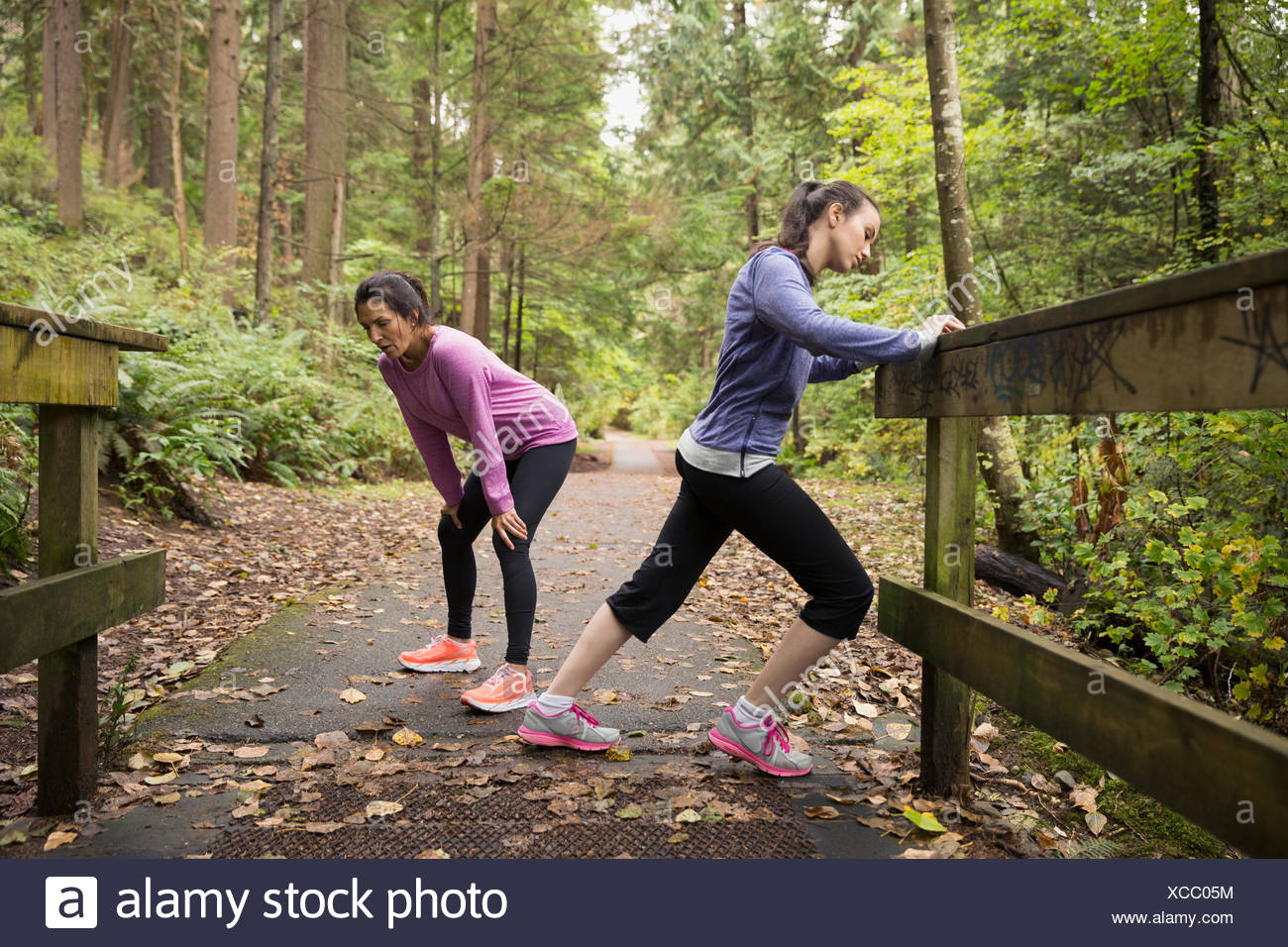 Mother and daughter stretching after run in woods - Stock Image