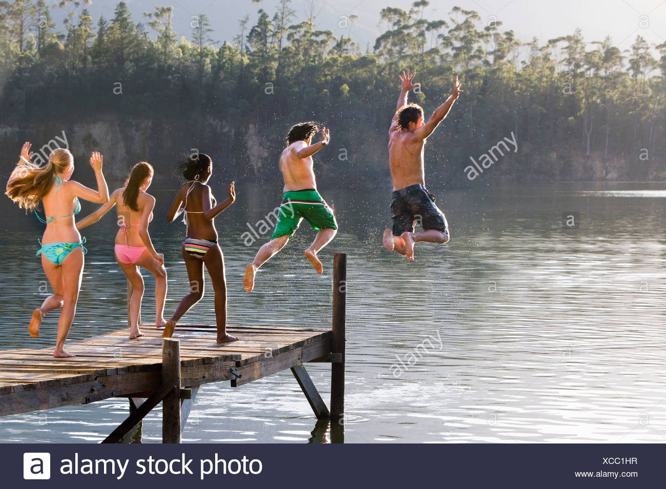Five young adults in swimwear jumping side by side from jetty into lake rear view - Stock Image
