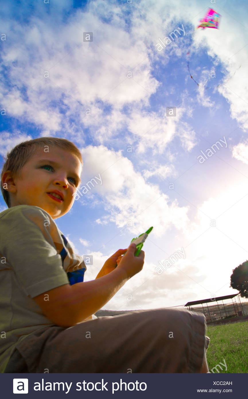 A youg boy's with autism attention has drifted away from his kite flying above him. - Stock Image