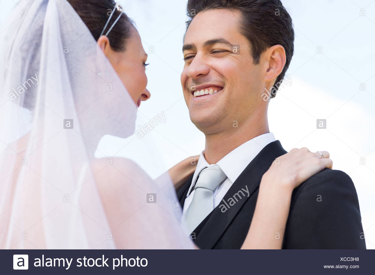 Happy newly wed couple against sky - Stock Image
