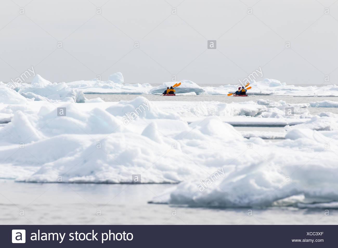 Canoeists amid icebergs on the sea ice edge of North Spitsbergen, Norway - Stock Image