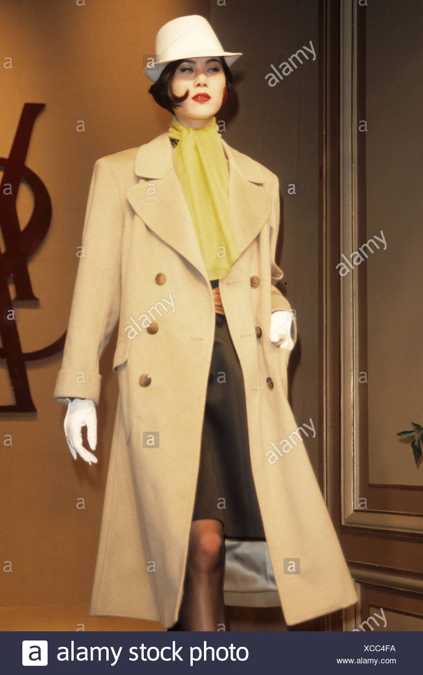 804f5f784f4 Yves Saint Laurent Spring Summer Female wearing beige mac over brown dress,  accessorized yellow scarf and beige trilby hat and