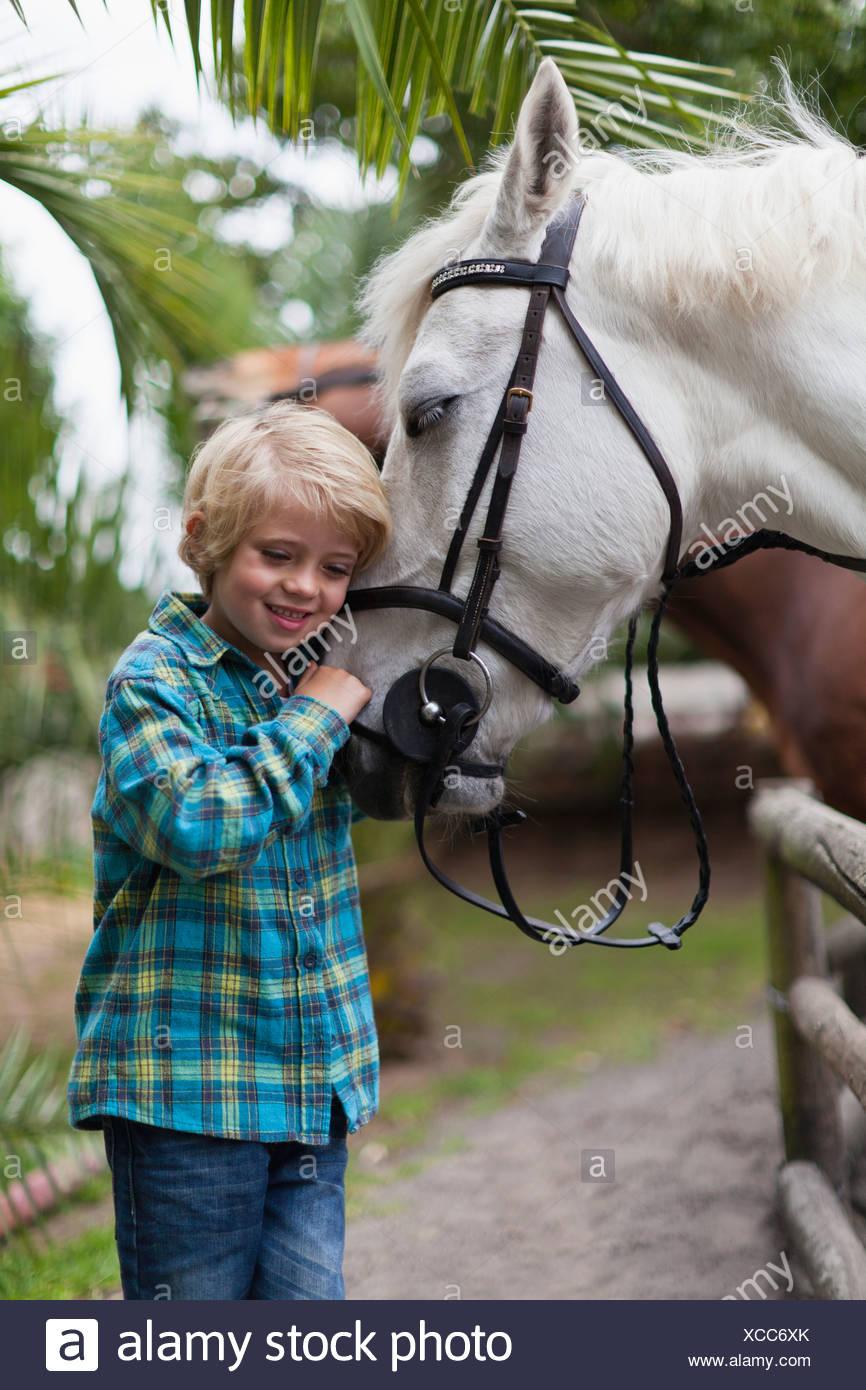 Boy hugging horse in yard - Stock Image
