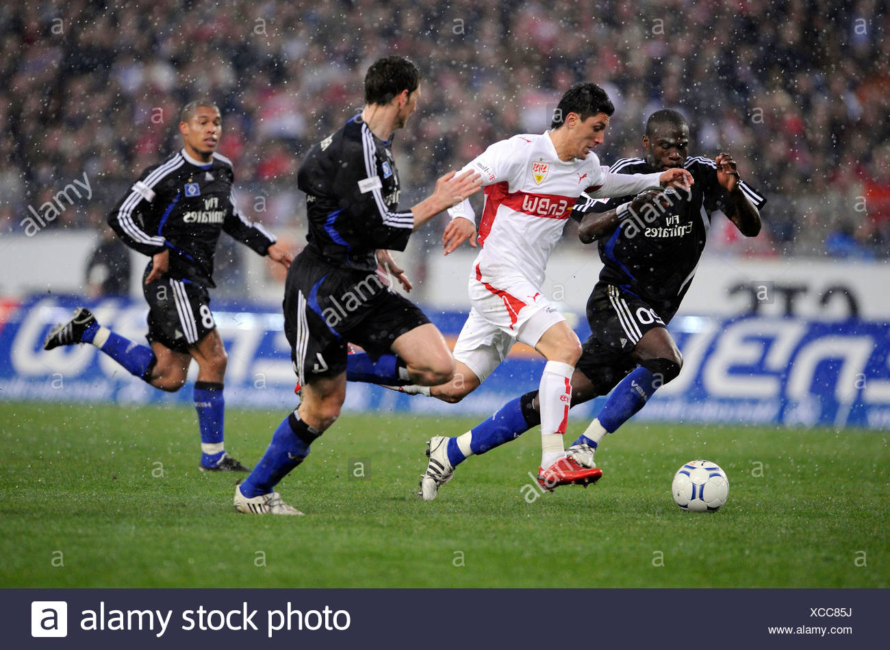 Tackle, Hamburg SV footballers Guy Demel (left) and Bastion Reinhardt (right) against VfB Stuttgart player Ciprian Marica (midd - Stock Image
