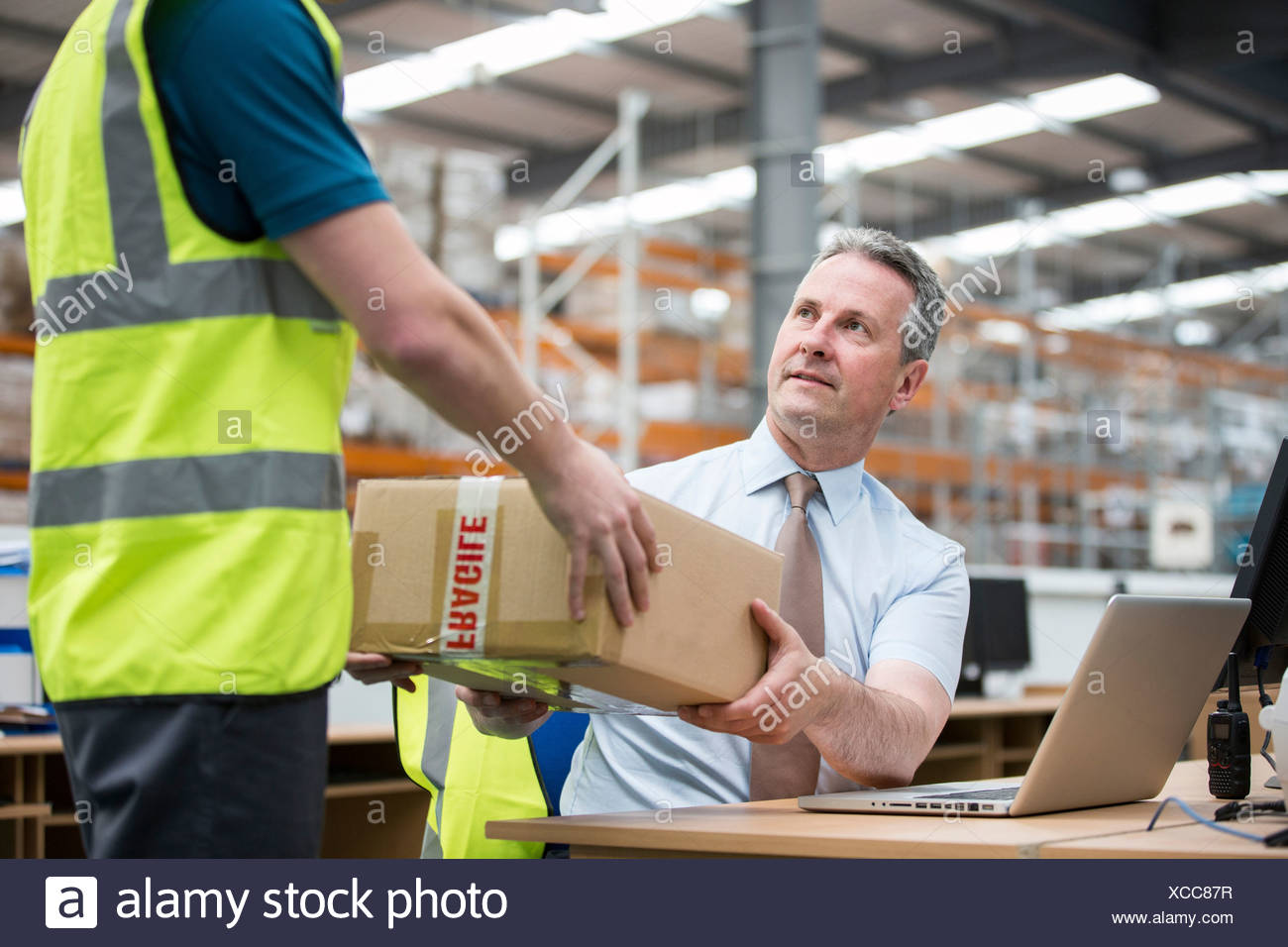 Man delivering cardboard box to another man - Stock Image