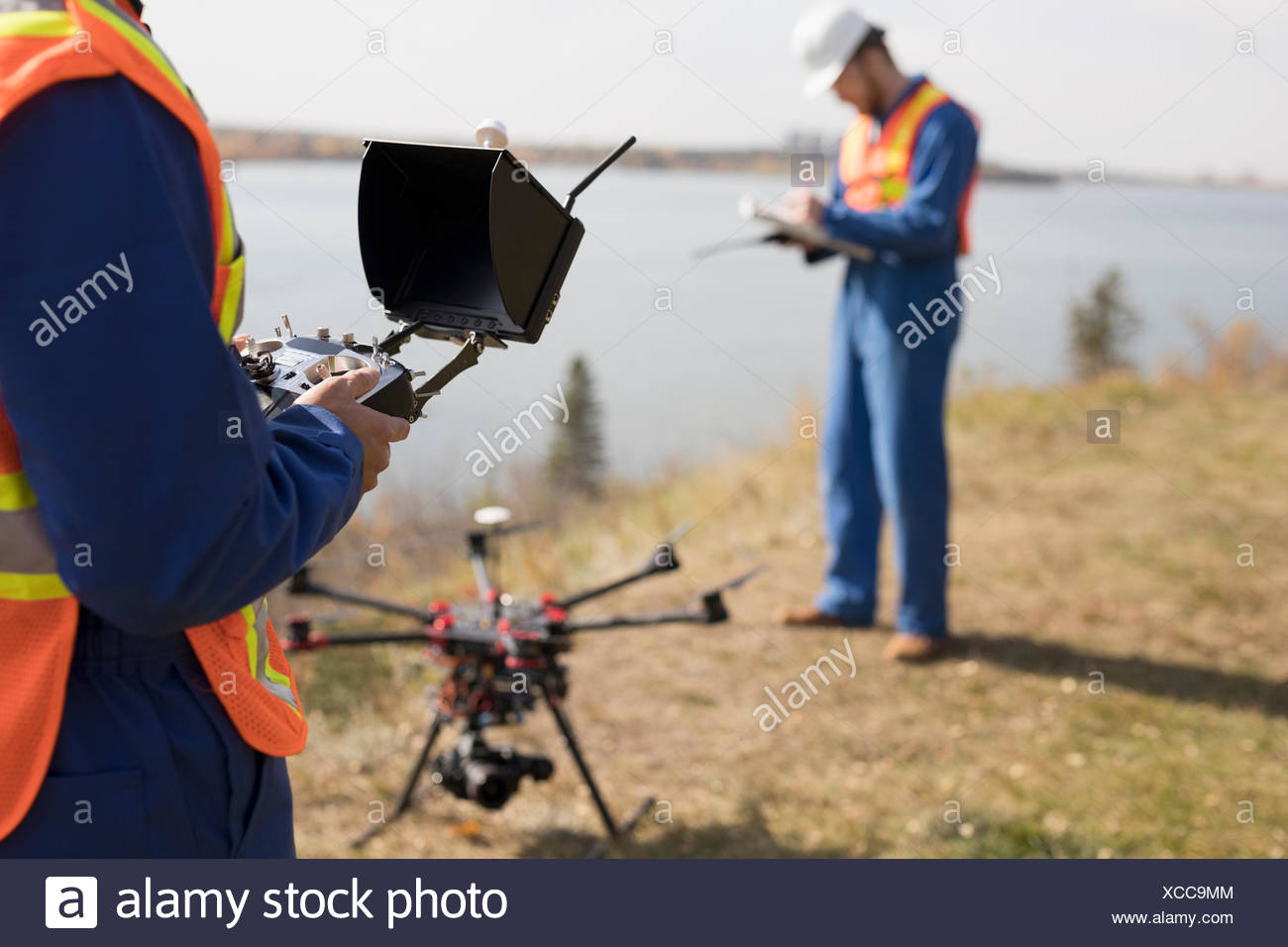 Surveyors with drone equipment at sunny lakeside - Stock Image