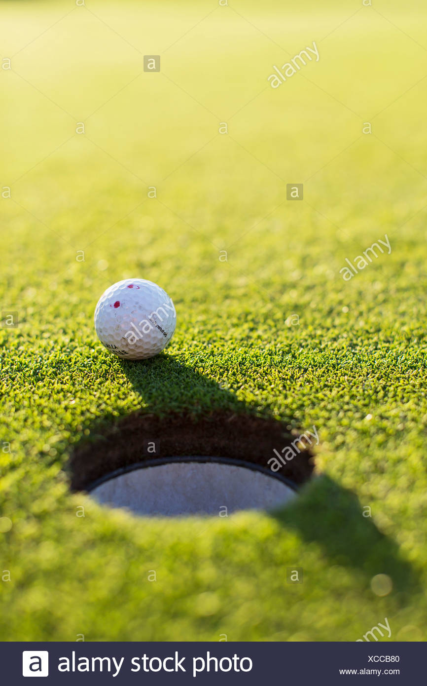 Golf ball by hole - Stock Image
