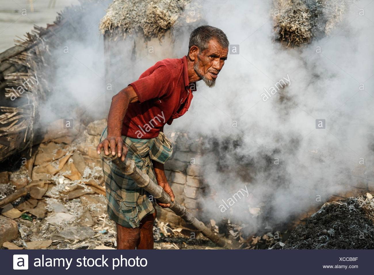 A man processes tannery wastes to make poultry feed at Hazaribagh along the polluted Buriganga river in Dhaka. - Stock Image