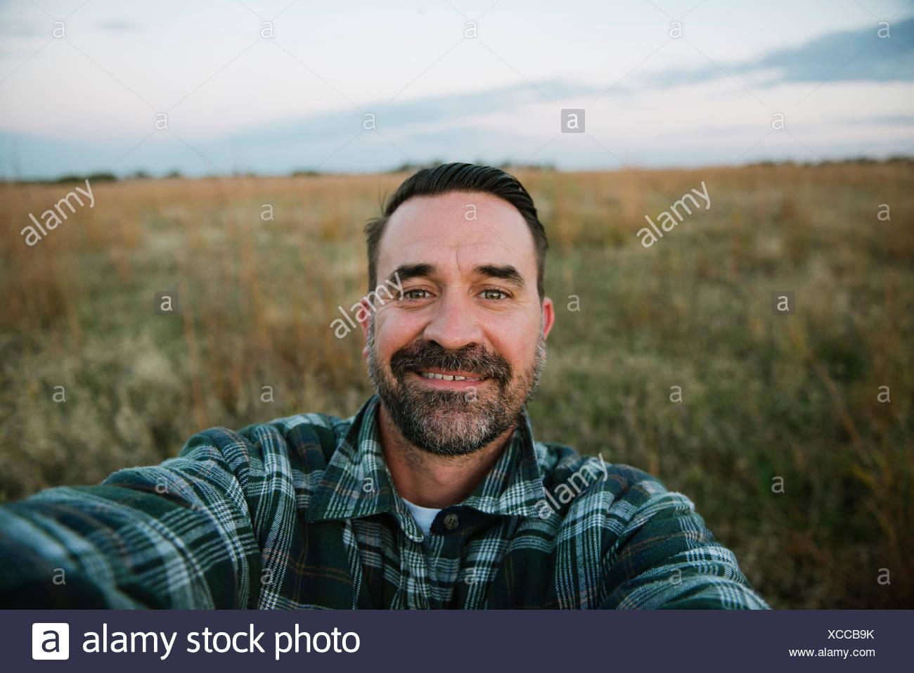 Self portrait of smiling farmer in field, Plattsburg, Missouri, USA - Stock Image