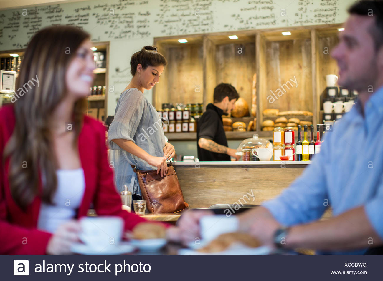 Couple talking in busy cafe - Stock Image