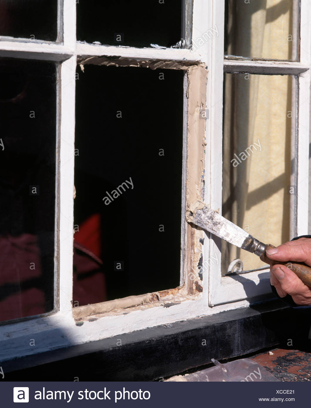 Close-up of hands applying putty to a newly replaced window pane - Stock Image