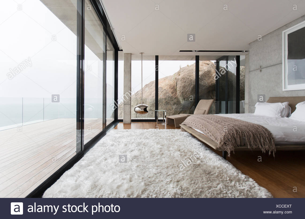 Shag rug and glass walls in modern bedroom - Stock Image