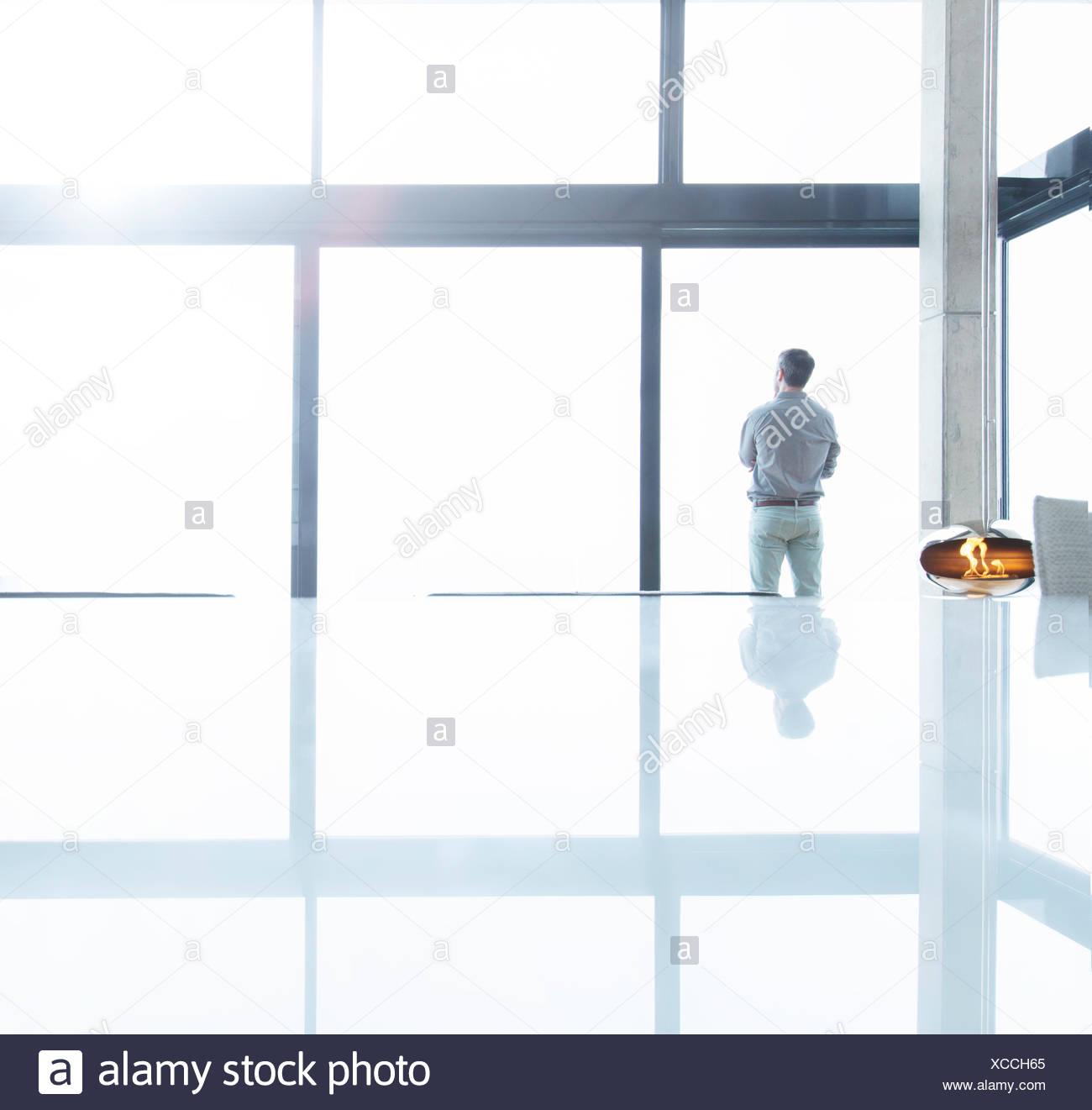 Businessman standing at office window - Stock Image