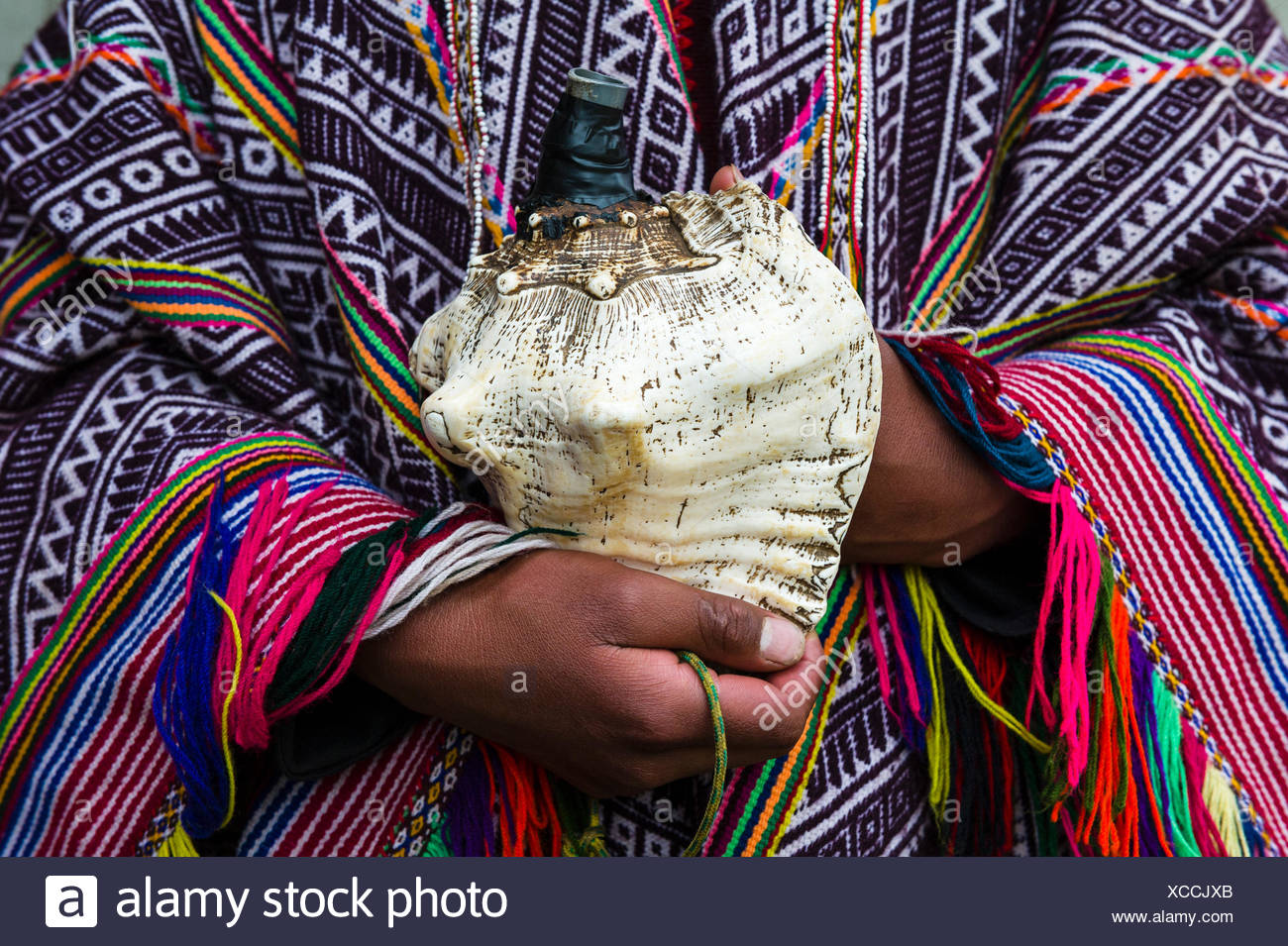 An Amaru man wearing a colourful handwoven poncho holding a shell horn. - Stock Image